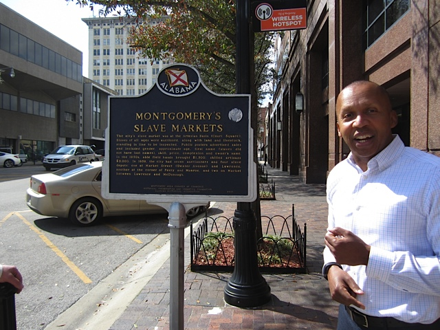 Bryan Stevenson with sign of Montgomery Slave Market